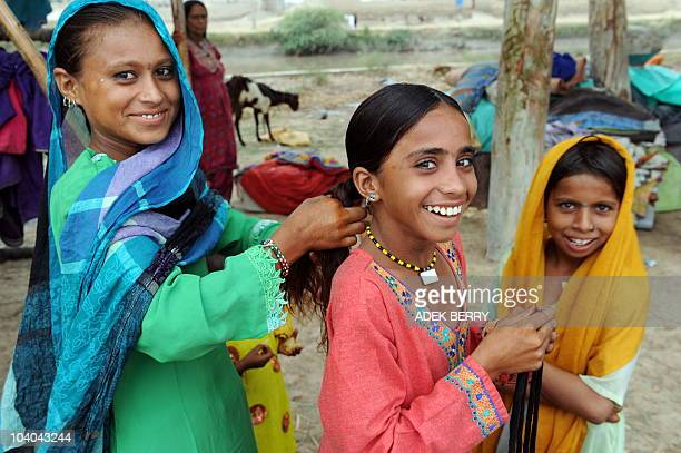 Internally displaced Pakistani girls living on the road prepare to celebrate Eid AlFitr in Sukkur on September 11 2010 Pakistani Muslims on September...