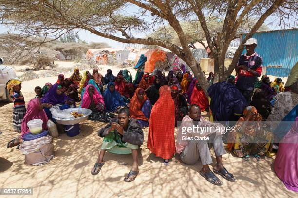 MOGADISHU SOMALIA MARCH 7 2017 Internally Displaced Persons gather under Acacia trees outside a World Food Program aid center at the 'KM13' camp on...