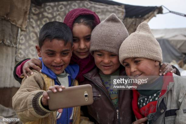 Internally Displaced Syrian kids fled from their homes due to the Assad Regime forces' attacks on civilians and siege for more than 6 years pose for...