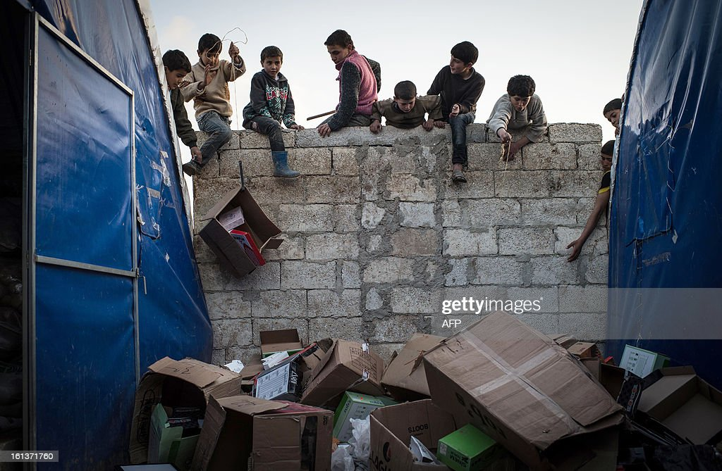 Internally displaced Syrian refugee children climb up a wall as they collect empty boxes at a refugee camp at Azaz along the Syrian-Turkish border on February 10, 2013. Some 15,000 refugees, mainly from the northern regions of Syria are living in this camp with no running water or electricity, in winter temperature that drop to under zero centigrade at night. AFP PHOTO/EDOUARD ELIAS