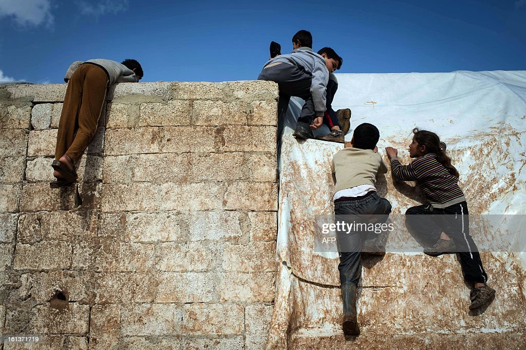 Internally displaced Syrian refugee children climb up a wall at a refugee camp at Azaz along the Syrian-Turkish border on February 10, 2013. Some 15,000 refugees, mainly from the northern regions of Syria are living in this camp with no running water or electricity, in winter temperature that drop to under zero centigrade at night.