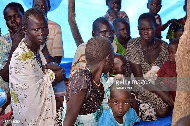 Internally displaced women and children sit in a tent in Ganyiel village of Panyijar County of Unity State on March 21 2015 WFP Executive Director...