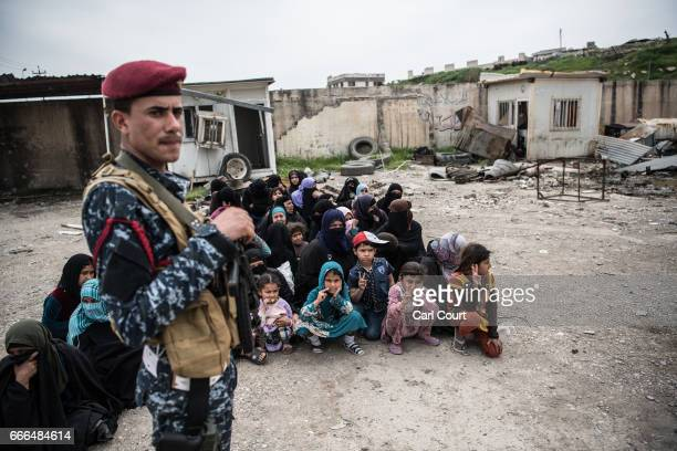 Internally displaced women sit on the ground as they wait to be checked by security forces during fighting in west Mosul on April 8 2017 in Mosul...