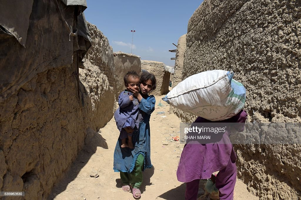 Internally-displaced Afghan children walk at a refugee camp in Kabul on May 31, 2016. The number of people internally displaced by war in Afghanistan has doubled since 2012 to 1.2 million, Amnesty International said on May 31, citing government neglect and a lack of international attention. In its report entitled 'My children will die this winter: Afghanistan's broken promise to the displaced', the rights group warned that a lack of basic services had pushed many of those uprooted from their homes to the brink of survival. / AFP / SHAH