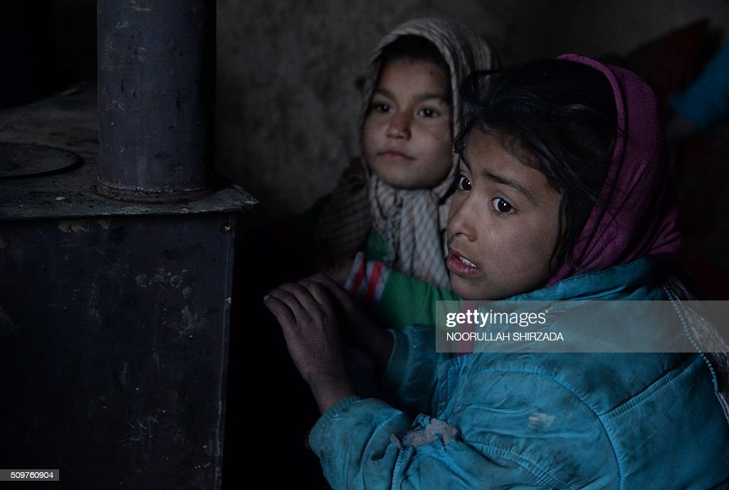 Internally-displaced Afghan children warm themselves around a stove at their temporary home on the outskirts of Kabul on February 12, 2016. As winter continues across Central Asia, many Afghans struggle to provide adequate food and shelter for their families. AFP PHOTO / Noorullah Shirzada / AFP / Noorullah Shirzada