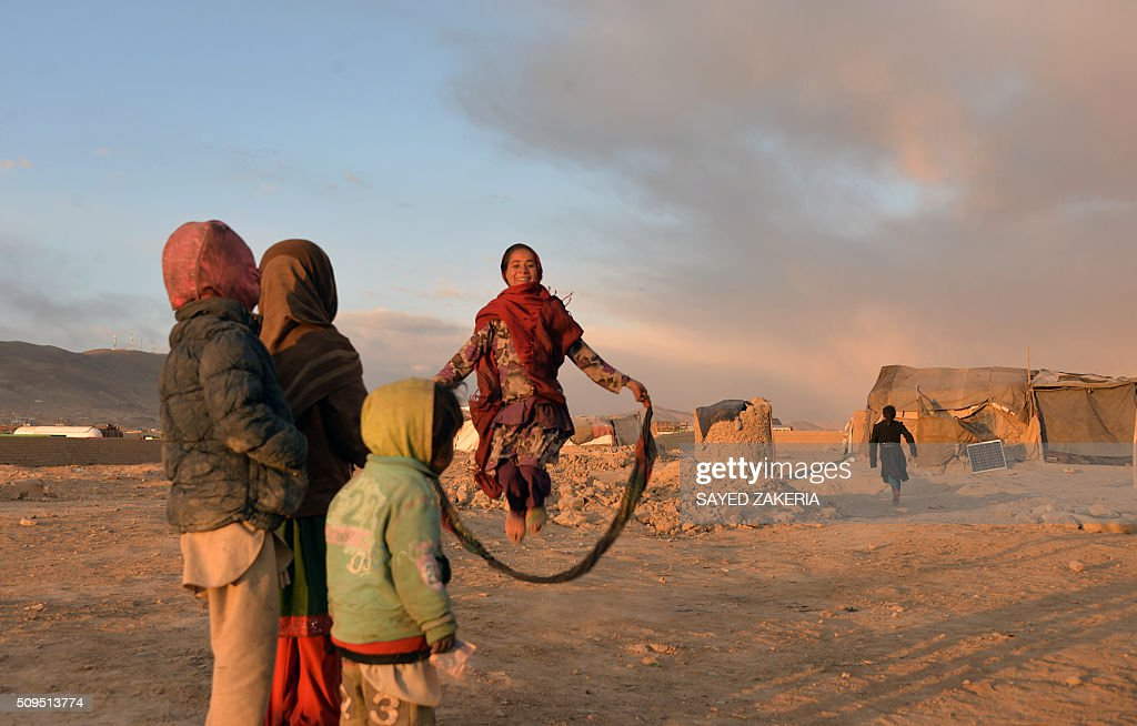 Internally-displaced Afghan children watch a girl jump with a skip rope at a refugee camp in Ghazni on February 11, 2015. AFP PHOTO / SAYED ZAKERIA / AFP / SAYED ZAKERIA