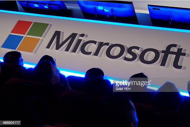 International buyers listen to a speeck in front of a Microsoft logo during the Computex tech show in Taipei on June 4 2014 More than 1500 exhibitors...