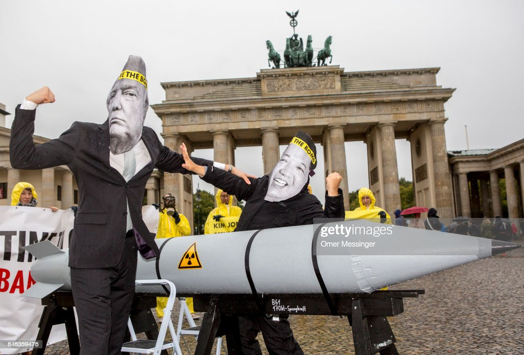 International campaign to abolish Nuclear Weapons (ICAN) activists wearing masks to look like US President Donald Trump and North Korean Kim Jong-Un pose next to a Styrofoam effigy of a nuclear bomb while protesting in front of the Brandenburg Gate near the American Embassy on September 13, 2017 in Berlin, Germany. The protests, which were organized by anti-nuclear and pro-peace group ICAN, took place at both the North Korean and US embassies.