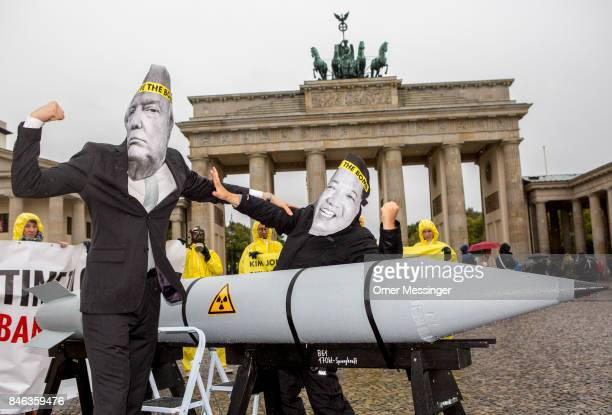 Activists wearing masks to look like US President Donald Trump and North Korean Kim JongUn pose next to a Styrofoam effigy of a nuclear bomb while...
