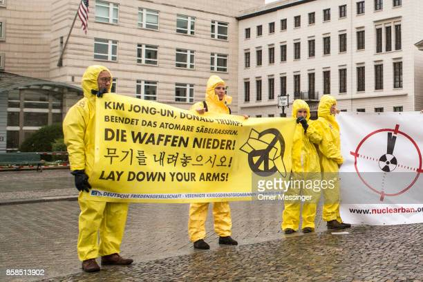 International campaign to abolish Nuclear Weapons activists wearing yellow hazmat suits and holding a banner reading 'Time to go ban nuclear weapons'...