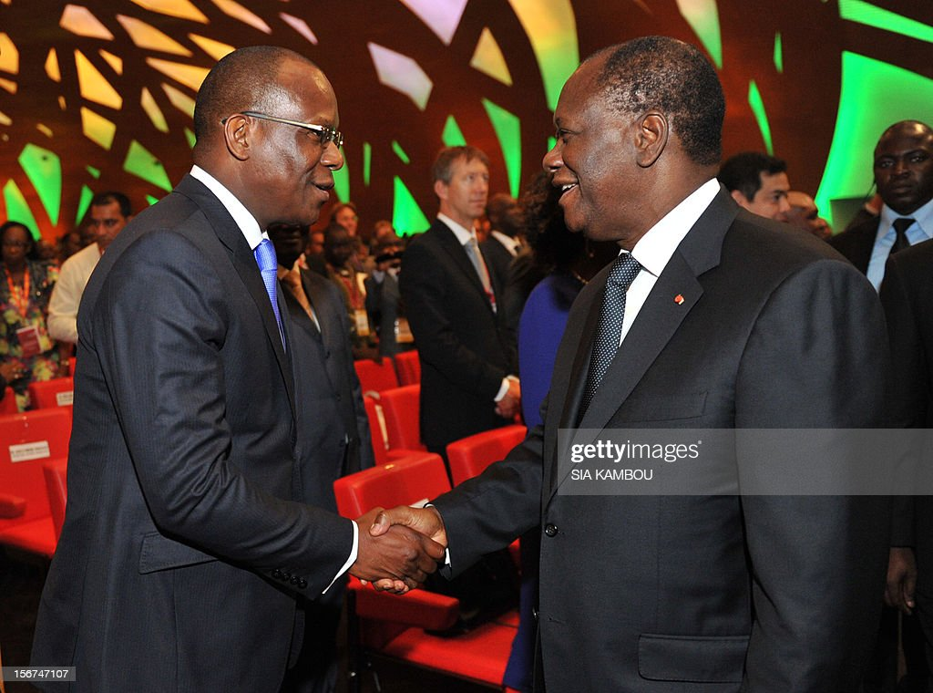 International Cocoa Organization (ICCO)'s CEO, Jean-Marc Anga shakes hands with Ivorian President Alassane Ouattara upon their arrival for during the opening of the 2012 World Cocoa conference in Abidjan. Ivory Coast on Tuesday hosts world players in the cocoa business for a conference on how to face up to the challenges posed by soaring demand. AFP PHOTO/ SIA KAMBOU