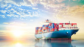 International Container Cargo ship in the ocean at sunset sky, Freight Transportation, Nautical Vessel