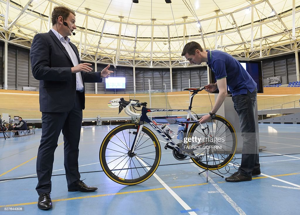 International Cycling Union (UCI) technical manager Mark Barfield (L) gestures next to a staff member holding a tablet to scan a bicycle during a demonstation on testing technological fraud and detecting the presence of a motor inside the frame at the UCI headquarters in Aigle, western Switzerland, on May 3, 2016. The tablet scans a bicycle with magnetic resistance technology, testing the frame and wheels in less than a minute in order to detect mechanical doping during cycling races. / AFP / FABRICE