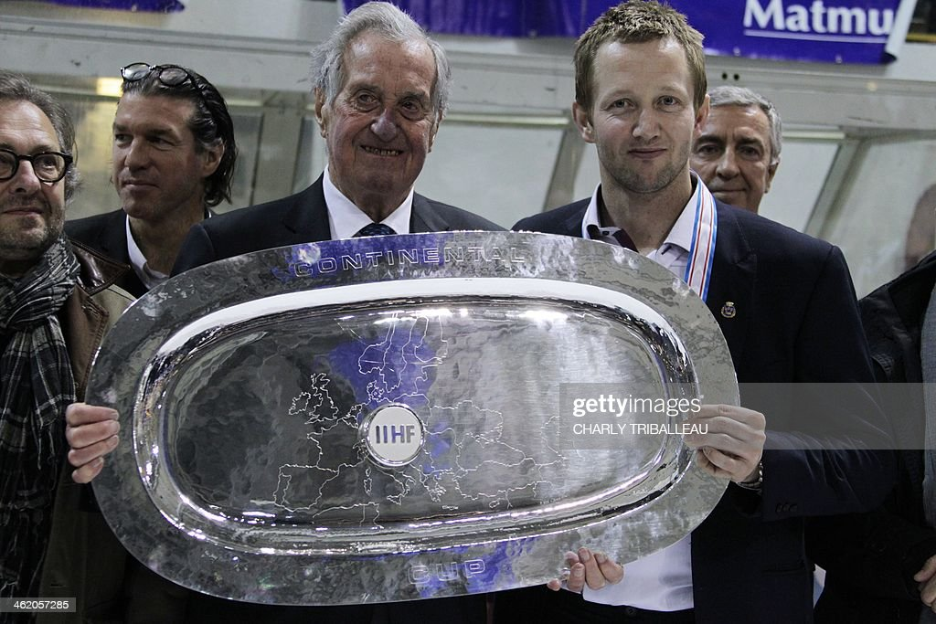International Ice Hockey Federation (IIHF) chairman Hans Dobida (Center L) gives the Continental Cup trophy to Stavanger player Snorre Hallem (Center R), at the end of the final Continental Cup Hockey League tournament on January 12, 2014, at the Ile Lacroix arena in Rouen, northwestern France.