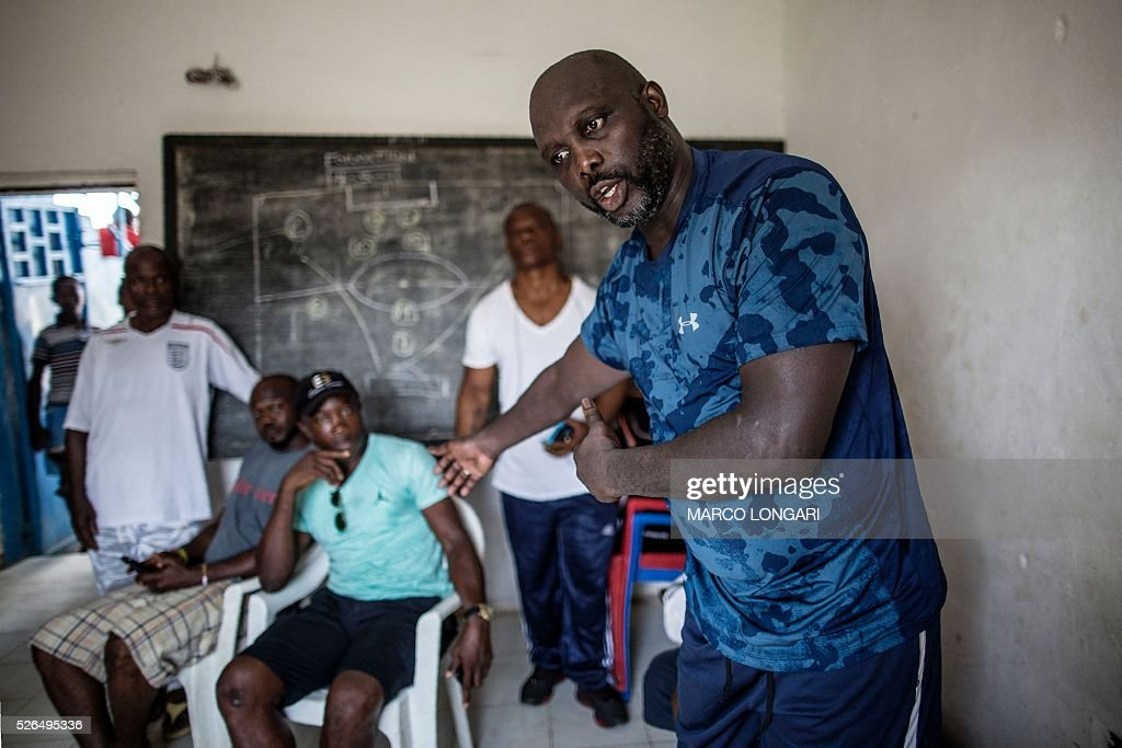 International Liberian soccer star, George Weah discusses with his team members at the end of a match played on a dusty pitch at the Alpha Old Timers Sports Association in Paynesville in Monrovia on April 30, 2016. Former international football star George Weah said on April 28, 2016, he would be a candidate in next year's presidential elections in Liberia, his second bid for the post. / AFP / MARCO