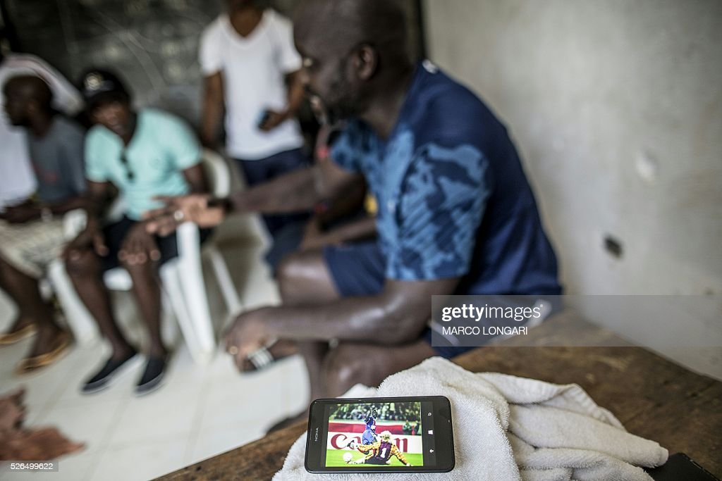 International Liberian soccer star, George Weah discusses with members of his team as a picture of himself scoring a goal wearing the jersey of Paris Saint Germain is shown on a smart phone, at the end of a match played on a dusty pitch at the Alpha Old Timers Sports Association in Paynesville in Monrovia on April 30, 2016. Former international football star George Weah said on April 28, 2016, he would be a candidate in next year's presidential elections in Liberia, his second bid for the post. / AFP / MARCO