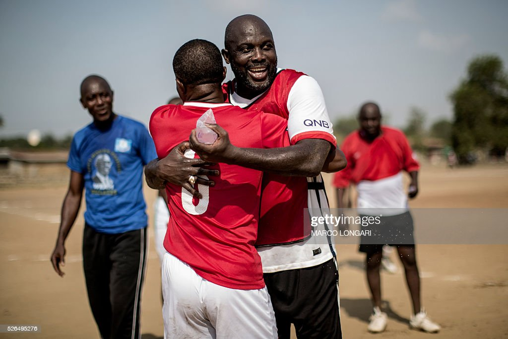 International Liberian soccer star, George Weah embraces a team member at the end of a match played on a dusty pitch at the Alpha Old Timers Sports Association in Paynesville in Monrovia on April 30, 2016. Former international football star George Weah said on April 28, 2016, he would be a candidate in next year's presidential elections in Liberia, his second bid for the post. / AFP / MARCO