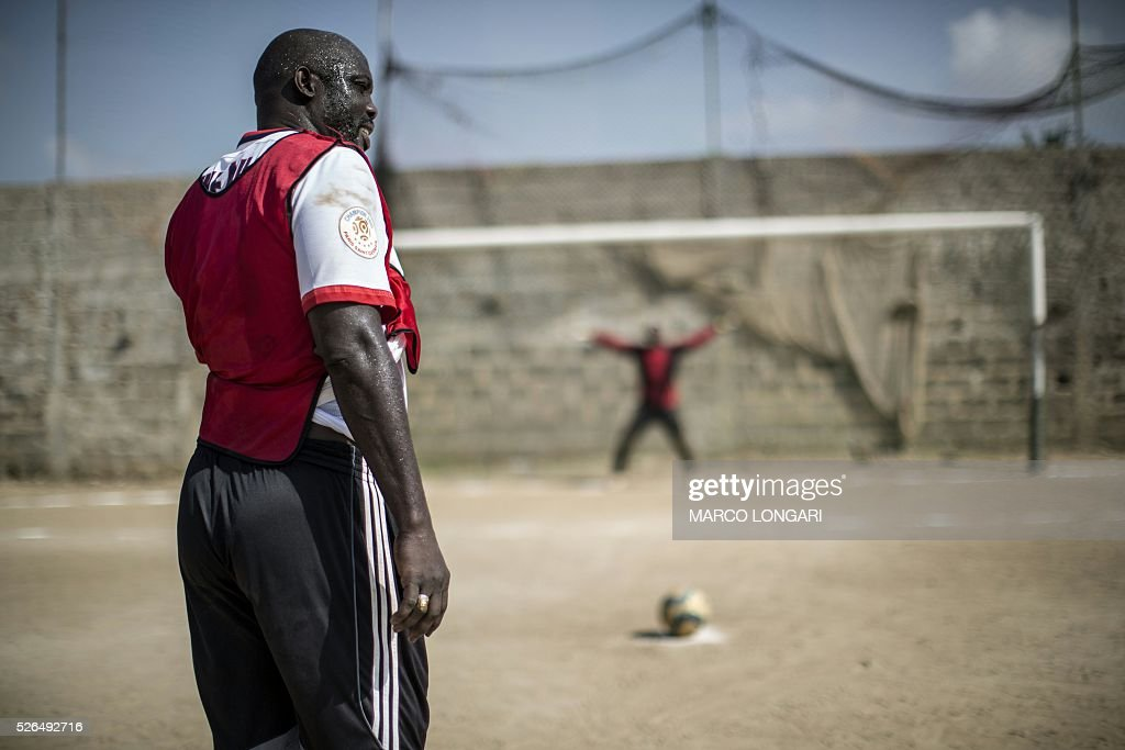 International Liberian soccer star, George Weah prepares to shoot a penalty during a match played on a dusty pitch at the Alpha Old Timers Sports Association in Paynesville in Monrovia on April 30, 2016 . Former international football star George Weah said on April 28, 2016, he would be a candidate in next year's presidential elections in Liberia, his second bid for the post. / AFP / MARCO