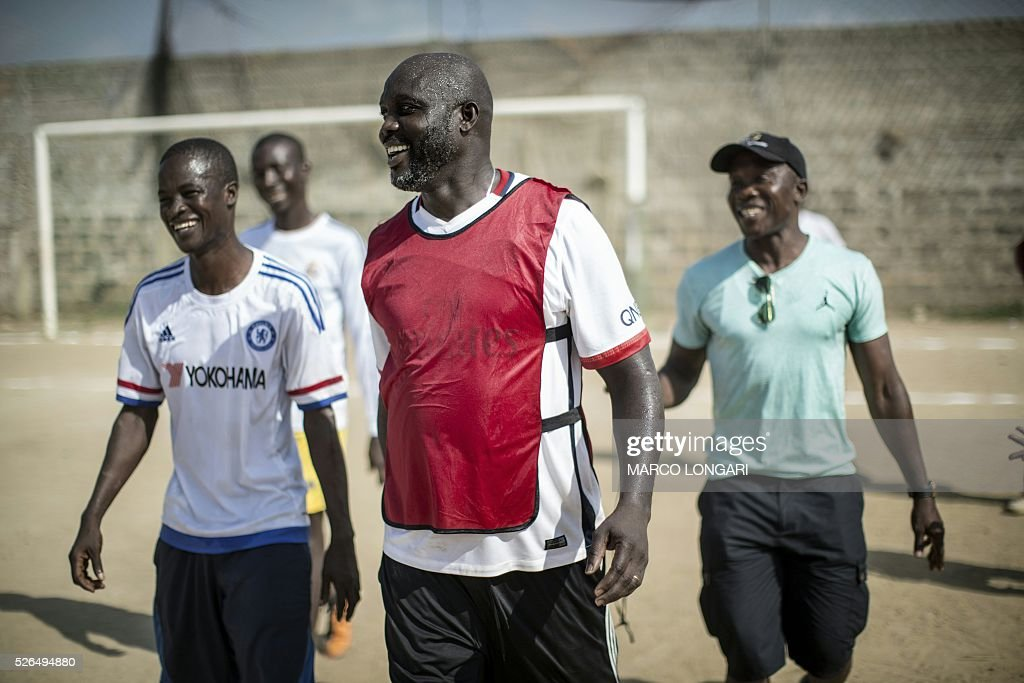 International Liberian soccer star, George Weah smiles with members of the opposite team after scoring a penalty during a match played on a dusty pitch at the Alpha Old Timers Sports Association in Paynesville in Monrovia on April 30, 2016. Former international football star George Weah said on April 28, 2016, he would be a candidate in next year's presidential elections in Liberia, his second bid for the post. / AFP / MARCO