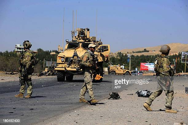 International military forces walk at the site of an attack on the US consulate in Herat on September 13 2013 Seven heavily armed Taliban suicide...