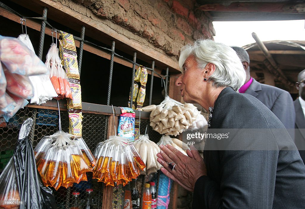 International Monetary Fund Managing Director Christine Lagarde greets a woman at a makeshift shop which was started thanks to a small loan given ny a micro-finance agency, at Kasengere village in the suburb of Malawi's capital Lilongwe, on January 5, 2013. The owner of the shop, Joylet Saidi, started her business after getting a loan from the MicroLoan Foundation which receives funds from the International Monetary Fund and distributes them to three local non-profit groups which help empower women - Nteza, Angola, and Chisangalalo. Lagarde urged Malawi to diversify its economy, saying a reliance on agriculture left the country's economic recovery under President Joyce Banda vulnerable. Lagarde is on a three day visit to Malawi from January 4 to January 6. AFP PHOTO / AMOS GUMULIRA