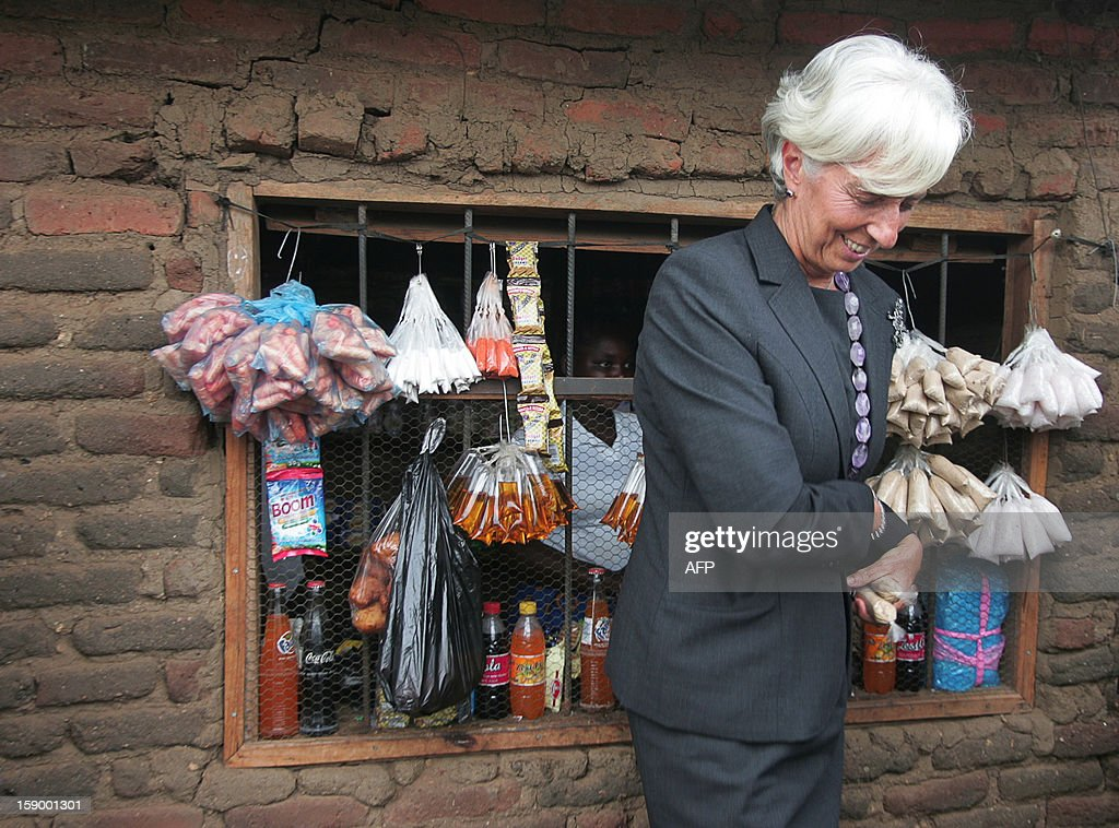 International Monetary Fund Managing Director Christine Lagarde walks away after buying small packets of sugar from a woman at a makeshift shop which was started thanks to a small loan given ny a micro-finance agency, at Kasengere village in the suburb of Malawi's capital Lilongwe, on January 5, 2013. The owner of the shop, Joylet Saidi, started her business after getting a loan from the MicroLoan Foundation which receives funds from the International Monetary Fund and distributes them to three local non-profit groups which help empower women - Nteza, Angola, and Chisangalalo. Lagarde urged Malawi to diversify its economy, saying a reliance on agriculture left the country's economic recovery under President Joyce Banda vulnerable. Lagarde is on a three day visit to Malawi from January 4 to January 6.