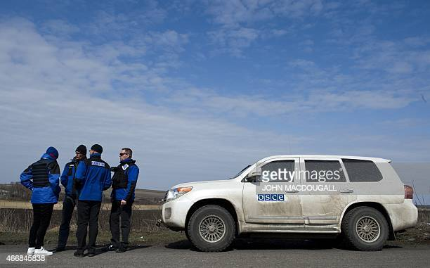International observers of the OSCE wait at a checkpoint during a weapon inspection tour in Ulyanivske some 100 km east of Donetsk close to Ukraine's...