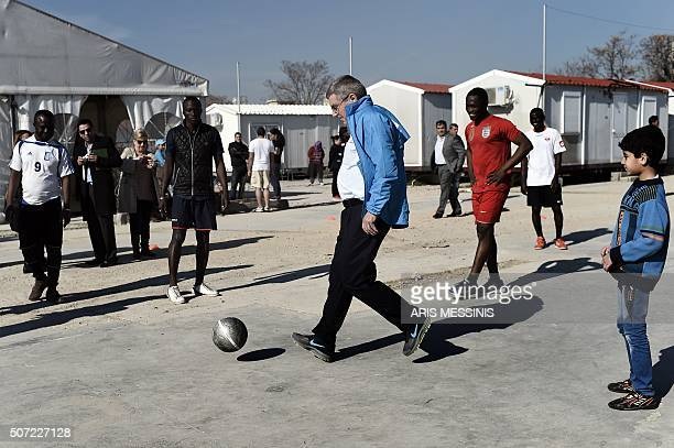 TOPSHOT International Olympic Committee chairman Thomas Bach plays football with youths during a visit to the Elaionas camp for migrants and refugees...