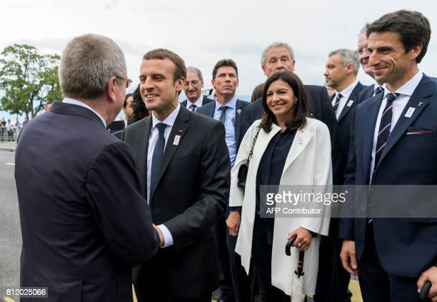 International Olympic Committee President Germany's Thomas Bach greets French President Emmanuel Macron watched by Mayor of Paris Anne Hidalgo French...