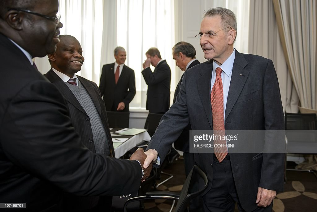 International Olympic Committee (IOC) president Jacques Rogge (R) shakes hands at the opening of an executive board meeting on December 4, 2012 in Lausanne. AFP PHOTO / FABRICE COFFRINI