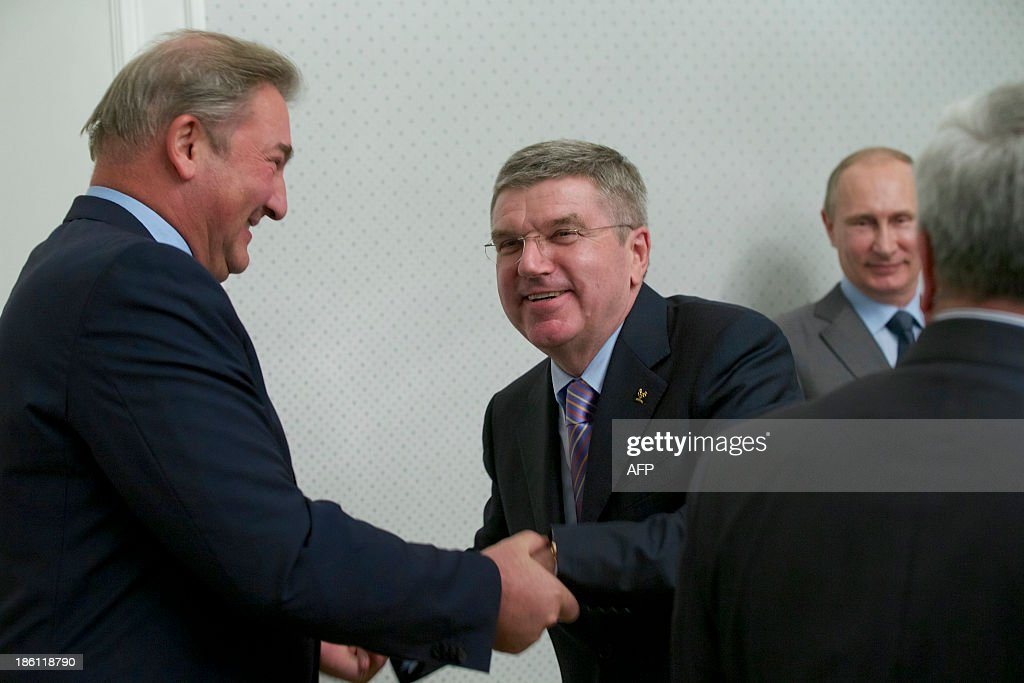 International Olympic Committee (IOC) President Thomas Bach (C) greets Soviet ice hockey legend, goalkeeper Vladislav Tretiak (L), as Russia's President Vladimir Putin (R) smiles during their meeting at Bocharov Ruchei residence in the Russian Black Sea resort of Sochi, on October 28, 2013. With a race against the clock to complete building works, threats of militant attacks and a controversy over an anti-gay law, Russia faces an unprecedented challenge to defeat its sceptics and hold a successful Sochi Winter Olympics in 100 days time.