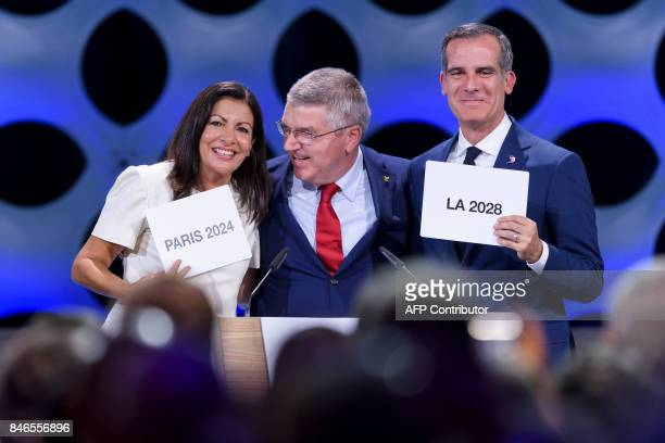 TOPSHOT International Olympic Committee President Thomas Bach poses for pictures with Paris Mayor Anne Hidalgo and Los Angeles Mayor Eric Garcetti...