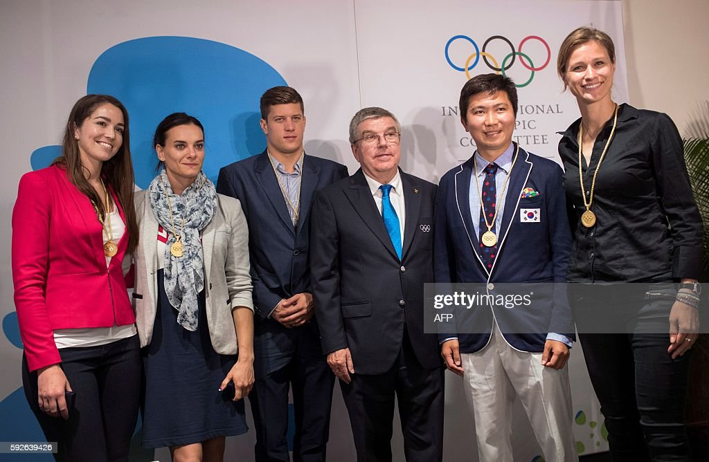 International Olympic Committee President Thomas Bach (3rd R) poses with newly elected members of the IOC Athletes Commission (from L) New Zealand BMX racer Sarah Walker, former Russian pole vaulter Yelena Isinbayeva, Hungarian swimmer Daniel Gyurta, South Korean table tennis player Ryu Seung-min and German epee fencer Britta Heidemann during the IOC 129th Session at the 2016 Summer Olympics in Rio de Janeiro on August 21, 2016. / AFP / POOL / Felipe Dana