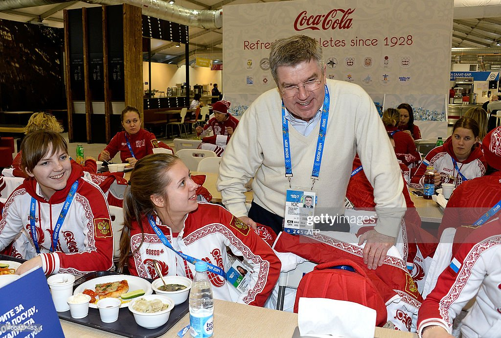 International Olympic Committee (IOC) President Thomas Bach (C) speaks with Ice hockey players Anna Shokhina (L) and Yelena Dergachyova of Russia at the Athletes Olympic Village prior to the start of the Sochi 2014 Winter Olympics on February 1, 2014 in Sochi. AFP PHOTO/POOL/ Pascal Le Segretain