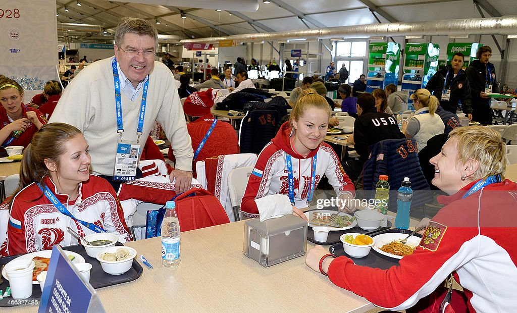 International Olympic Committee (IOC) President Thomas Bach (2L) speaks with (L-R) ice hockey players Yelena Dergachyova, Angelina Goncharenko and Yekaterina Pashkevich of Russia at the Athletes Olympic Village prior to the start of the Sochi 2014 Winter Olympics on February 1, 2014 in Sochi. AFP PHOTO/POOL/ Pascal Le Segretain