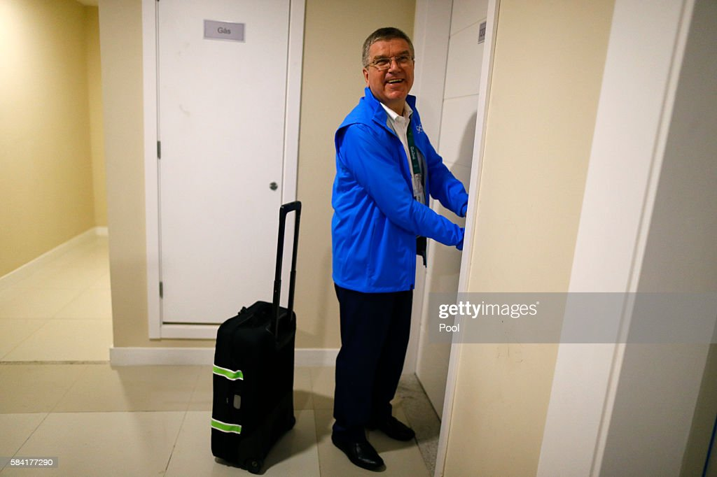 International Olympic Committee President Thomas Bach tries to open the door of his room as he moves into the Olympic village in Rio de Janeiro...