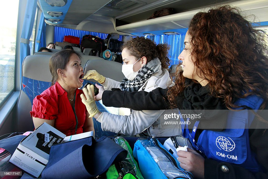 International Organisation for Migration (IOM) volunteers check a Filipino woman as Asian women who were working in Syria are seen inside a bus after they left the war-torn country with the help of IOM on December 11, 2012 at the Lebanese border with Syria. The workers headed to Beirut International Airport from where they flew to their respective countries.
