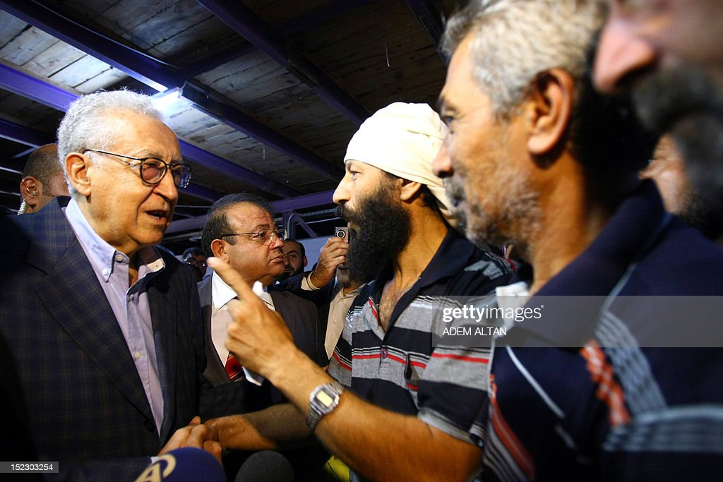 International peace envoy for Syria Lakhdar Brahimi (L) listens to a Syrian refugee as he visits the Altinozu camp in Hatay city, located on the border with their violence-racked homeland, on September 18, 2012. The Altinozu camp is one of the first refugee camps set up by Turkey soon after the unrest erupted in Syria mid-March 2011, which has already killed 20,000 according to UN figures and forced 250,000 to flee into neighbouring countries. AFP PHOTO / ADEM ALTAN