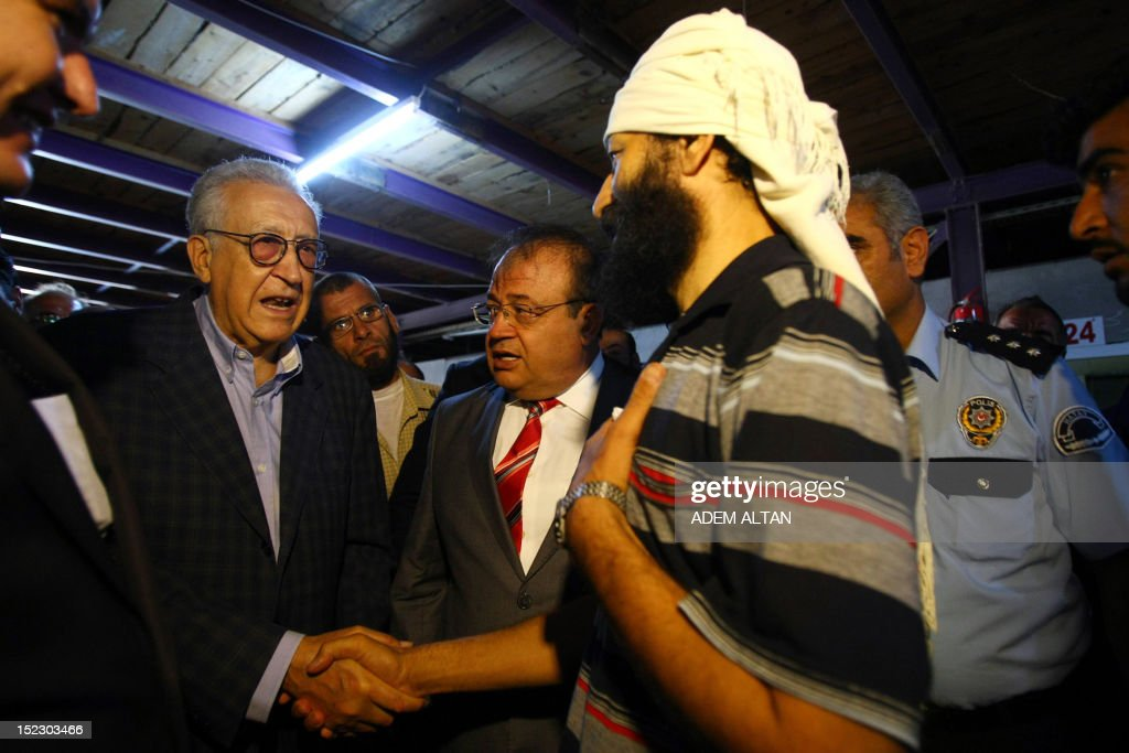 International peace envoy for Syria Lakhdar Brahimi (2ndL) speaks with a Syrian refugee as he visits the Altinozu camp in Hatay city, located on the border with their violence-racked homeland, on September 18, 2012. The Altinozu camp is one of the first refugee camps set up by Turkey soon after the unrest erupted in Syria mid-March 2011, which has already killed 20,000 according to UN figures and forced 250,000 to flee into neighbouring countries. AFP PHOTO / ADEM ALTAN