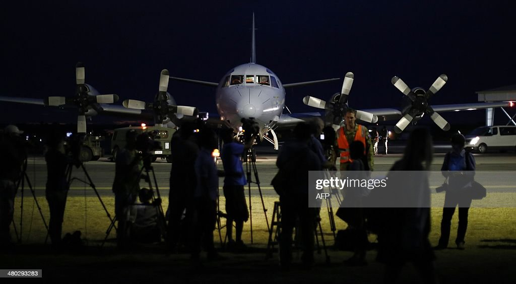 International press gather around a Royal Australian Air Force AP-3C Orion as it comes to rest upon its return from a search operation for the missing Malaysia Airlines flight MH370 over the Indian Ocean, at Pearce Airbase in Bullsbrook, 35 kms north of Perth on March 24, 2014. Malaysia Airlines revealed on March 24 the co-pilot of its missing jet was flying the Boeing 777 for the first time without a so-called 'check co-pilot' looking over his shoulder. AFP PHOTO/POOL/Jason REED