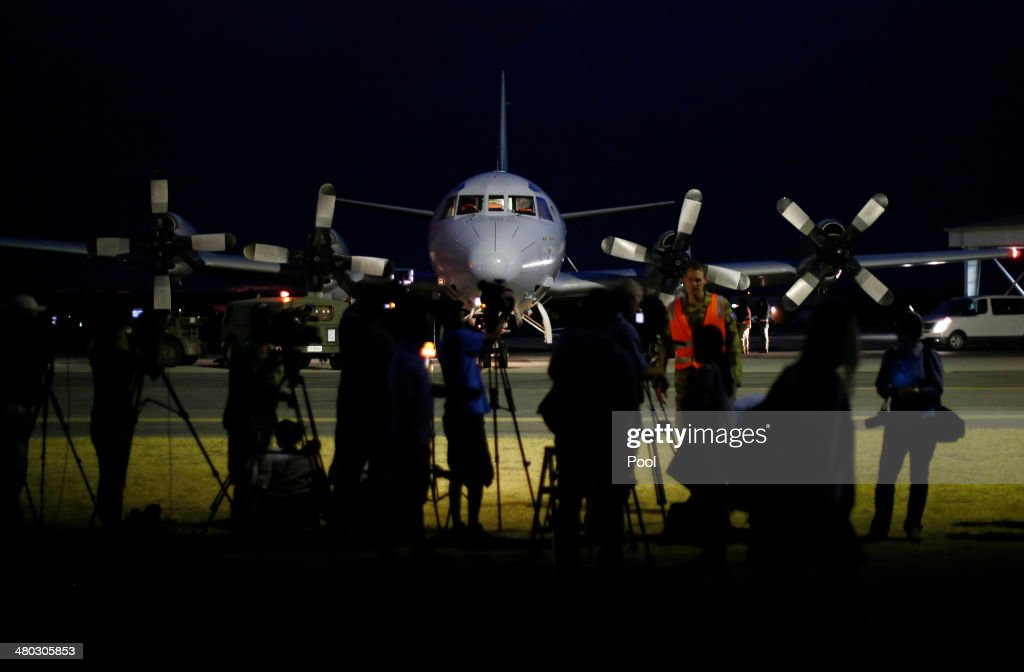 International press gather around a Royal Australian Air Force AP3C Orion upon its return from a search for Malaysian Airlines flight MH370 over the...