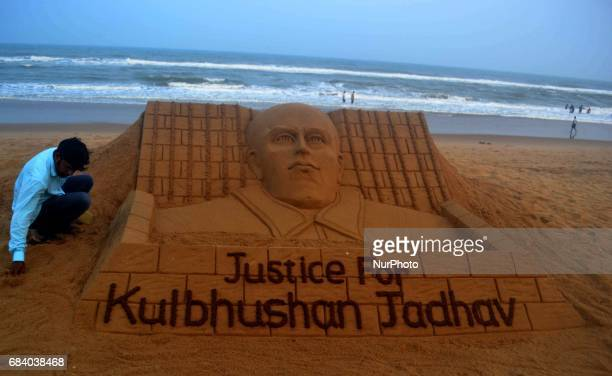 International sand artist Sudarshan Pattnaik gives the finishing touches to the sand sculpture at the Bay of Bengal Sea's eastern coast beach at Puri...