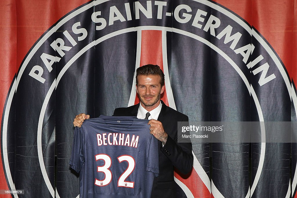 International soccer player David Beckham poses with his PSG Football shirt after his PSG signature at Parc des Princes on January 31, 2013 in Paris, France.