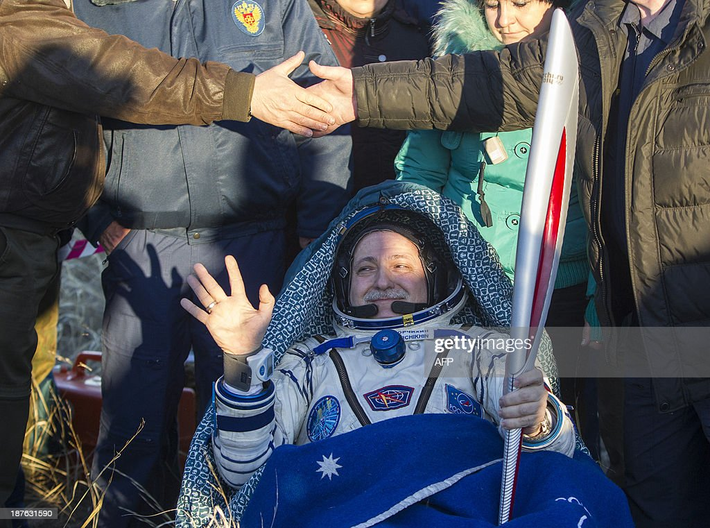 International Space Station (ISS) crew member Russian cosmonaut Fyodor Yurchikhin holds the torch of the 2014 Sochi Winter Olympic Games after landing in a remote area near the town of Zhezkazgan in central Kazakhstan on November 11, 2013. Three astronauts returned to Earth on November 11, after 66 days aboard the International Space Station, bringing back the Olympic torch back to the planet after a historic space walk. AFP PHOTO / Pool / Shamil Zhumatov