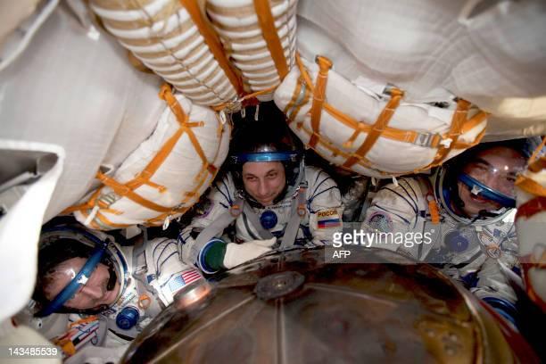 International Space Station crew members US astronaut Dan Burbank Russian cosmonauts Anton Shkaplerov and Anatoly Ivanishin sit inside the Soyuz...