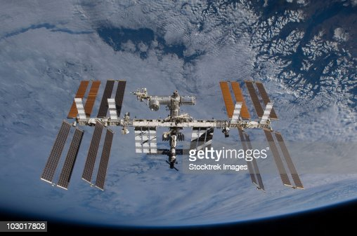 International Space Station set against the background of a cloud covered Earth.