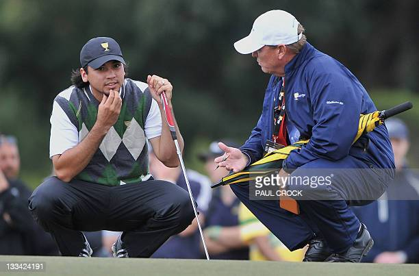 International team member Jason Day of Australia speaks to the match referee during the third day of the President's Cup golf tournament at the Royal...