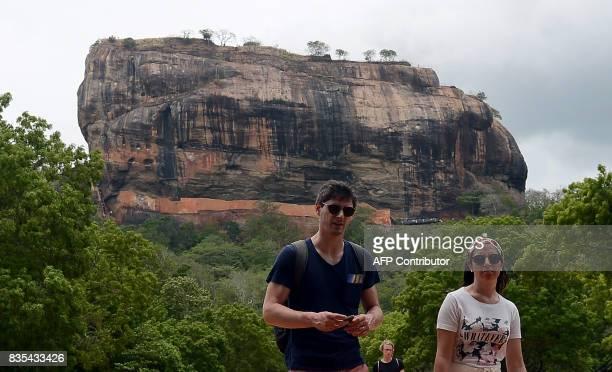 International tourists walk near Sigiriya Rock in Sigiriya northcentral Sri Lanka on August 19 2017 The Sigiriya rock 160 kilometres north of Colombo...