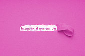 International womens day is celebrated on March 8 - text revealed by hole torn in pink paper background