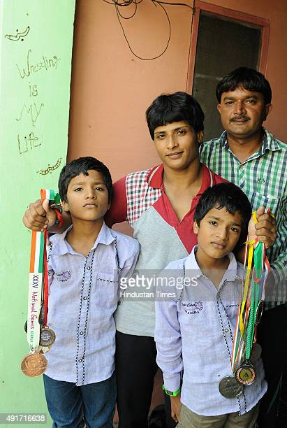 International wrestler Neetu with her husband Sanjay and twin sons Prince and Ayush at her village Bedwa on September 24 2015 in Rohtak India...